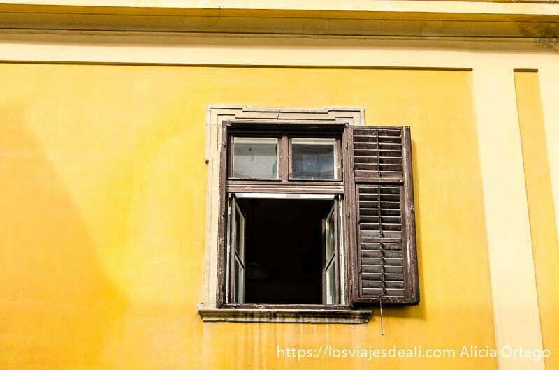 ventana de madera abierta en fachada de color amarillo qué ver en pécs