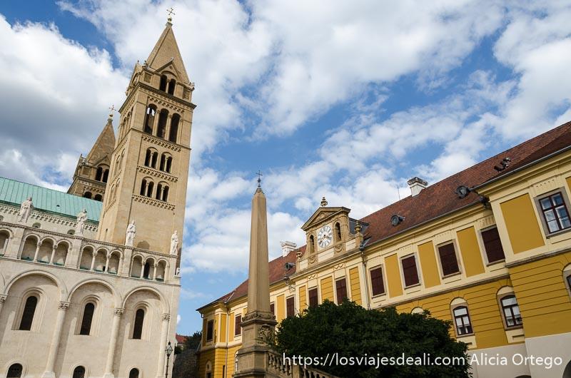 torre de la catedral y al lado edificio con muchas ventanas pintado de amarillo qué ver en pécs