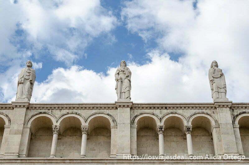 3 esculturas de reyes con su espada sobre muro de la catedral y nubes blancas de fondo qué ver en pécs