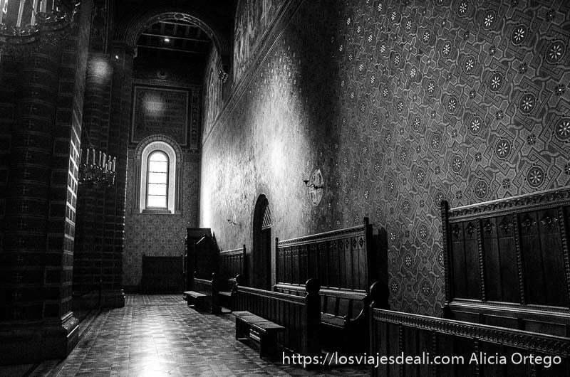 pasillo de la catedral con muro lleno de pinturas y bancos de madera grandes qué ver en pécs