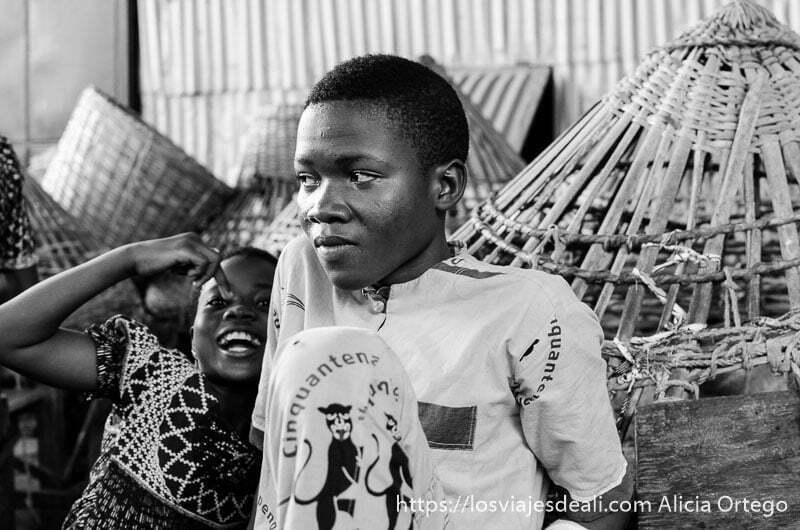 niño haciendo gracias a la cámara y adolescente mirando a otro lado  ruta en benin