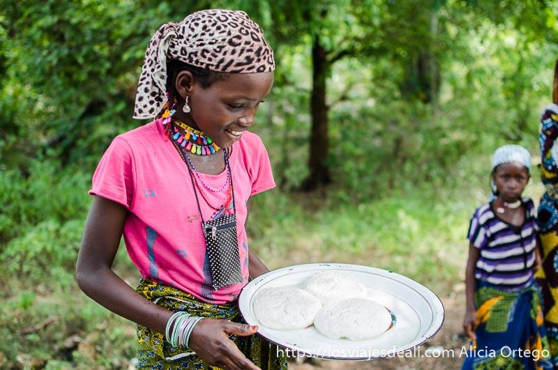 niña que vende queso fresco en la carretera con pañuelo en la cabeza y camiseta rosa ruta en benin
