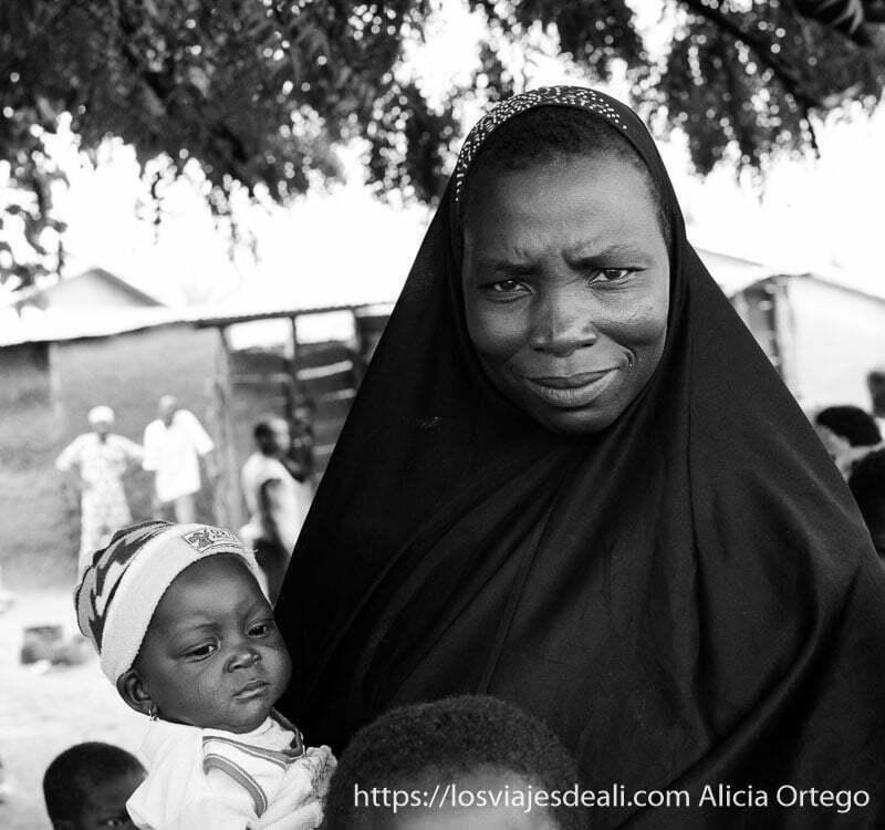 mujer negra con chador negro y bebé vestido de blanco en sus brazos ruta en benin