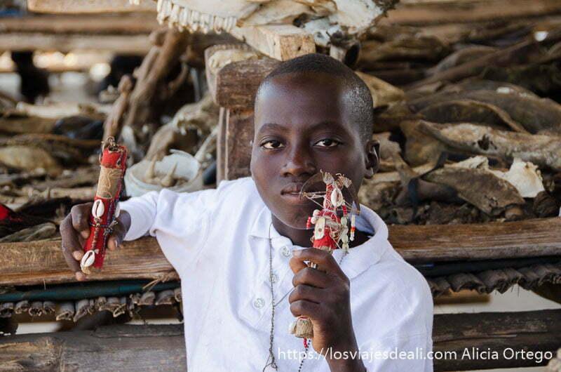 niño del mercado de fetiches de la capital de togo con dos muñecos vudú en la mano