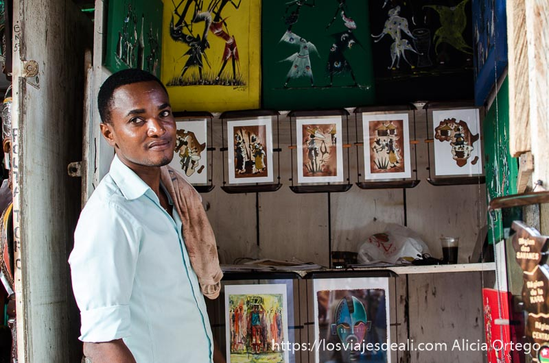 joven pintor junto a sus cuadros en la capital de togo lomé