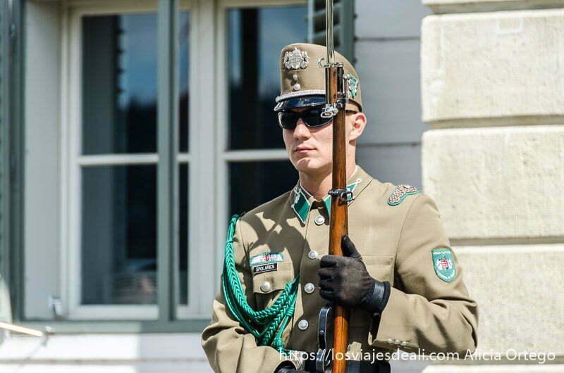 soldado con fusil y bayoneta y gafas de sol en la colina guía del budapest monumental