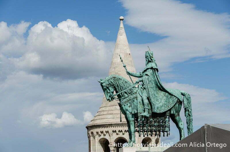 estatua de bronce de caballero y detrás torre del bastión de los pescadores de budapest