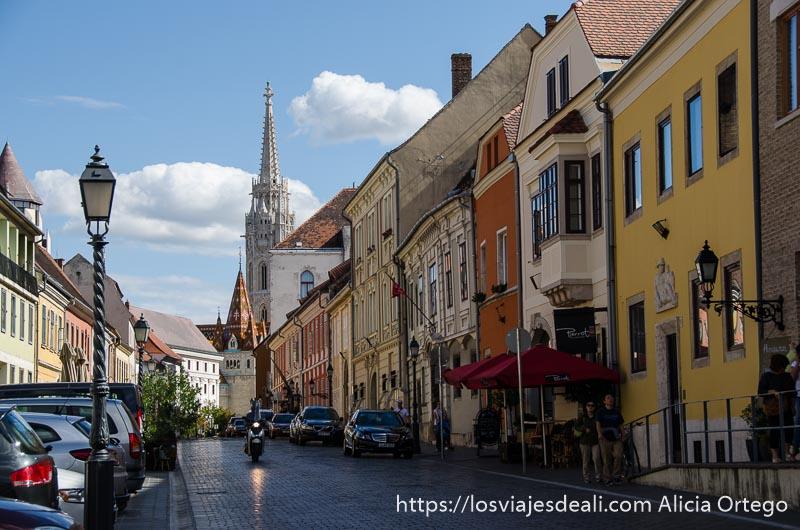calle con casas de colores y la torre de la iglesia al fondo guía del budapest monumental
