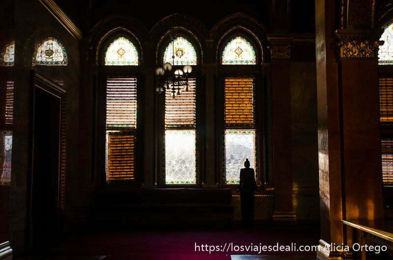 mujer mirando por los ventanales del parlamento guía del budapest monumental