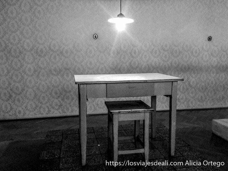 mesa de interrogatorio con lámpara encima en la casa del terror de budapest