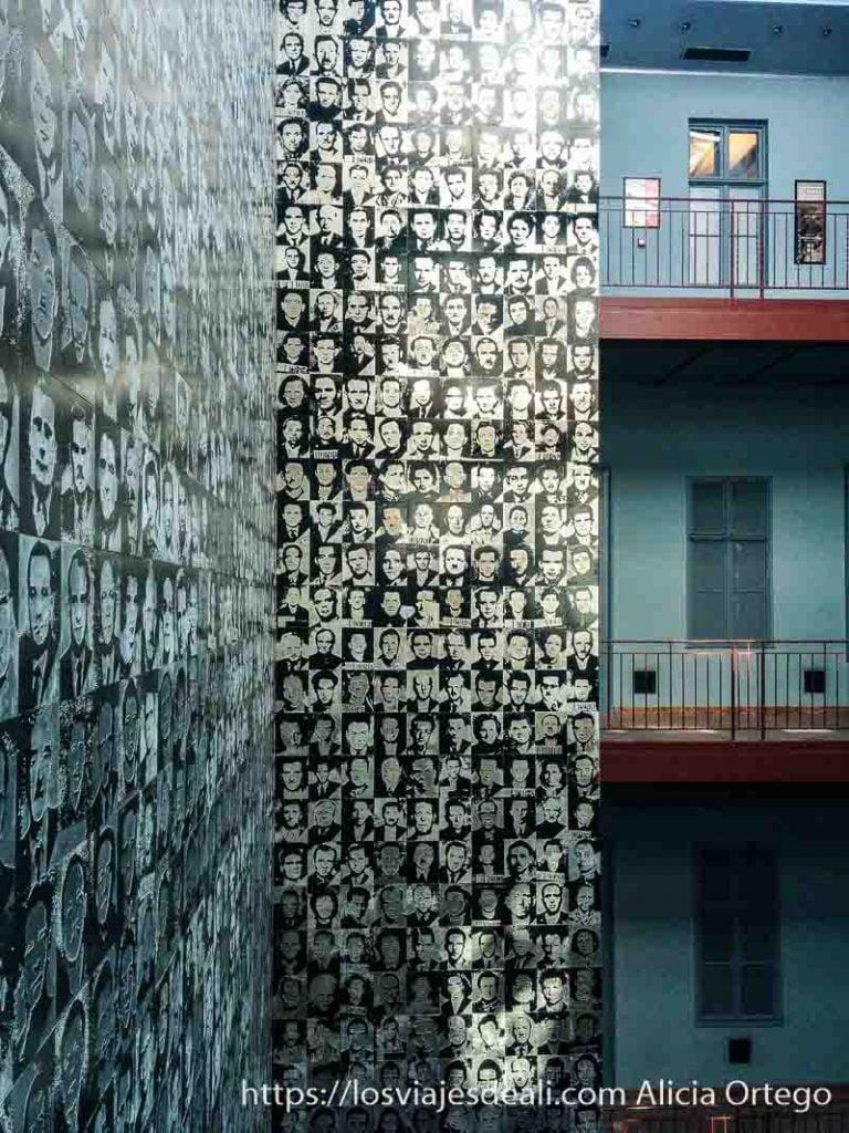 patio de la casa del terror con un mural gigante que cruza todos los pisos en vertical lleno de las fotos de los detenidos pasado comunista de budapest