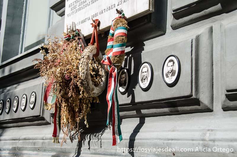 coronas funerarias con hojas ya secas y bandera húngara junto a las fotos de los desaparecidos en la casa del terror de budapest