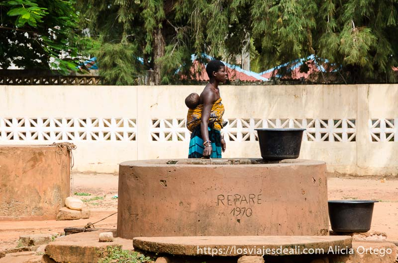 mujer pasando junto a un pozo con su bebé a la espalda sujeto con una tela en togoville