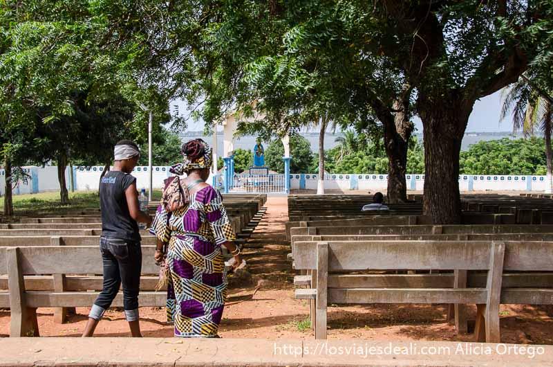 mujer vestida con telas africanas andando en el anfiteatro con la virgen al fondo y detrás el lago de togoville