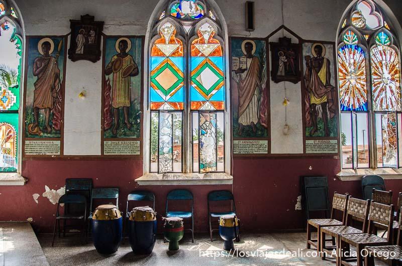 interior de la catedral de togoville con tambores djembé, sillas y pinturas con figuras africanas