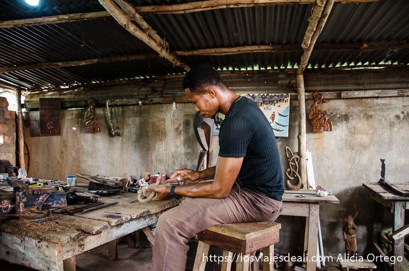 joven trabajando la madera en su taller de togoville