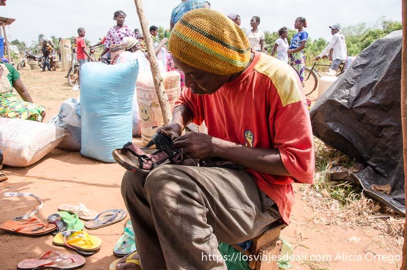 zapatero de togoville cosiendo mi sandalia sentado en un pequeño taburete al aire libre