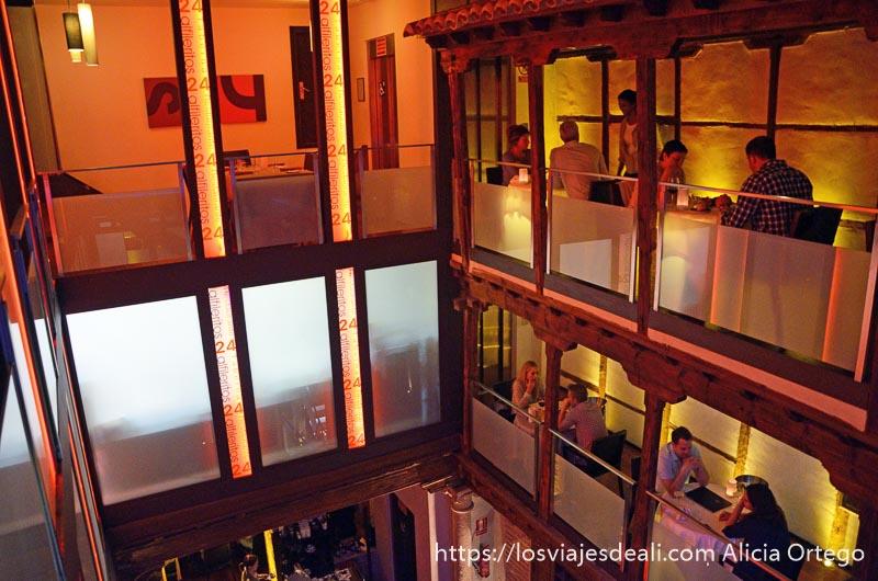 patio interior del restaurante 24 alfileritos de toledo con luces rojas y gente comiendo junto a los balcones