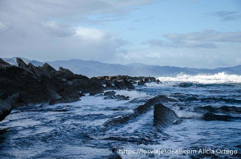 acantilados flysch medio cubiertos por el mar y olas al fondo
