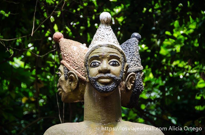escultura de dios con tres cabezas en el bosque sagrado de ouidah