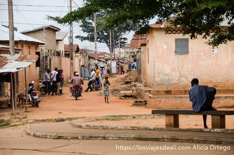 hombre sentado en un banco a la sombra de un árbol y calle con casas bajas todo con polvo rojo en ouidah historia de la esclavitud en benin