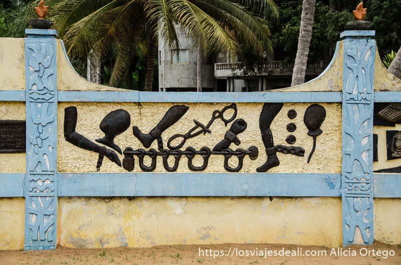 muro de almacén de esclavos con relieves pintados de negro de figuras de pies y manos encadenados historia de la esclavitud en benin