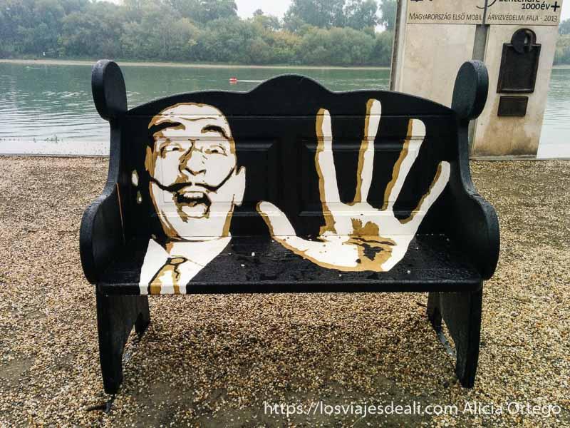 banco junto al río con retrato de Dalí poniendo mano abierta delante en szentendre