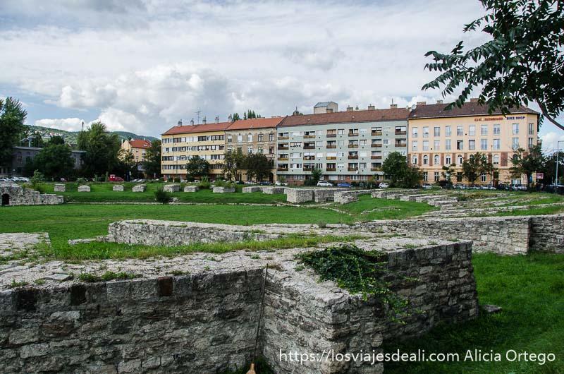 cimientos de edificios antiguos y al fondo bloques de casas soviéticas pintadas de colores en óbuda budapest