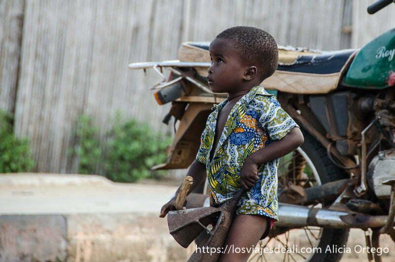 niño pequeño llevando un gran cencerro de hierro para tocar música en la ceremonia vudú