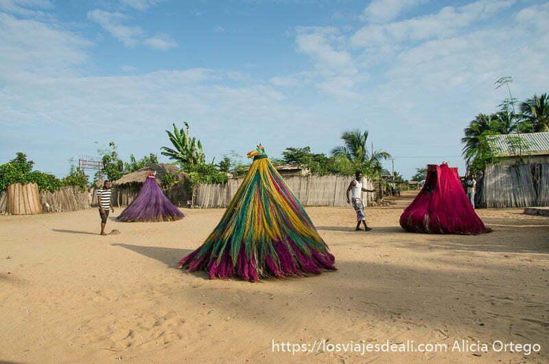 tres máscaras y dos sacerdotes bailando en la explanada de arena de la ceremonia vudú