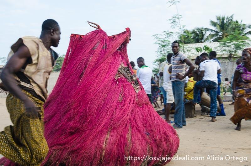 sacerdote corriendo junto a una máscara a gran velocidad en la ceremonia vudú