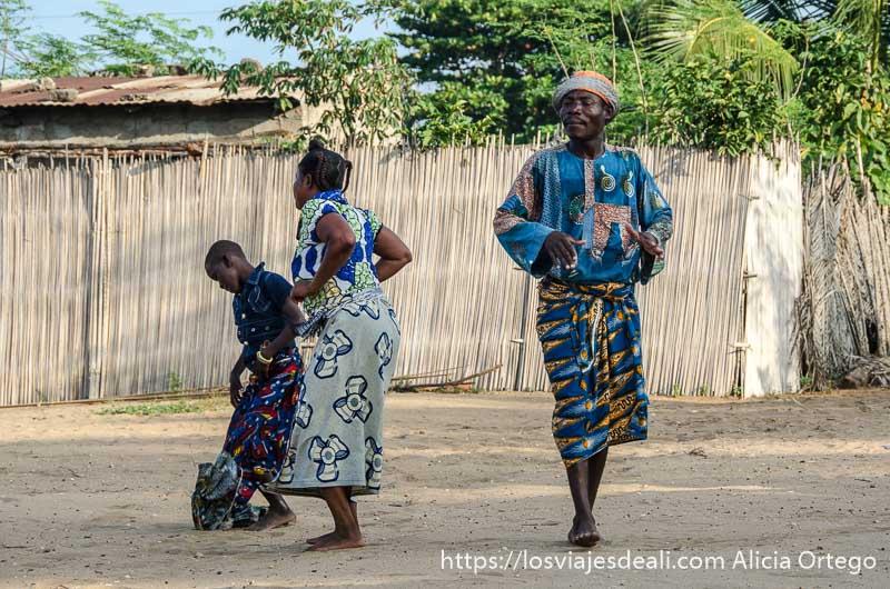 una mujer bailando con una niña y al lado un hombre con ojos cerrados sintiendo la música en la ceremonia vudú