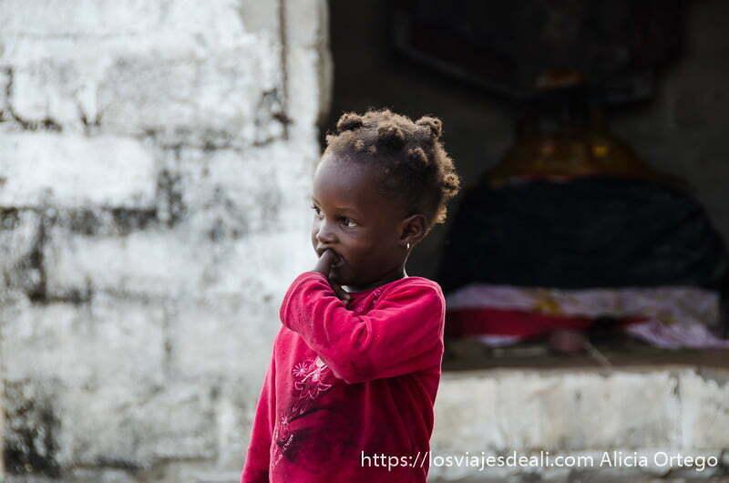 preciosa niña delante de la caseta donde está el dios mirando a la gente en ceremonia vudú