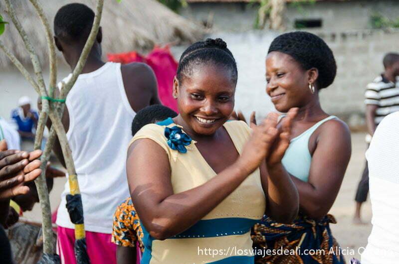 mujer sonriente dando palmas y mirando a sus hijos en la ceremonia vudú de benin