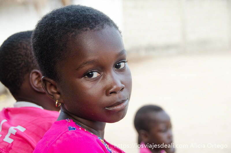 niña negra con camiseta fucsia en la ceremonia vudú de grand popó benin