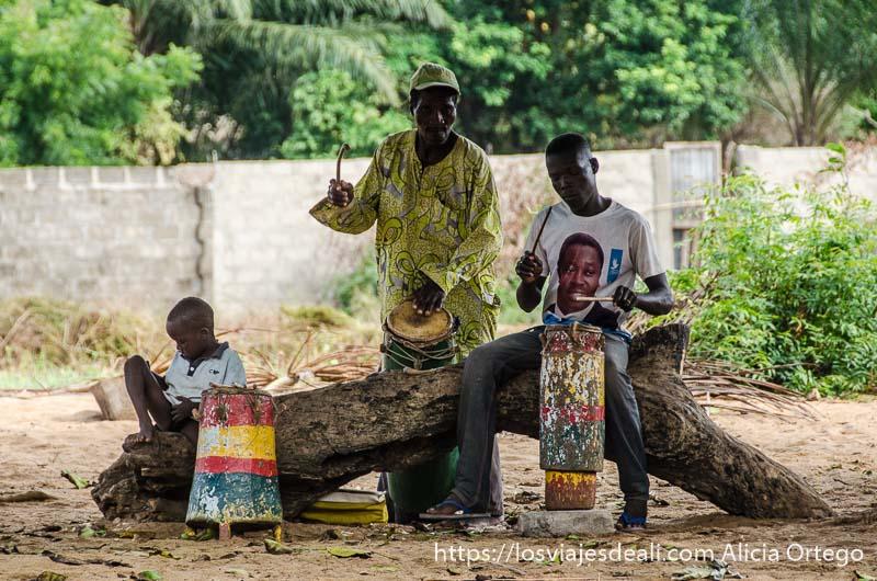 dos hombres tocando música con bidones sentados en el tronco de un árbol ceremonia vudú