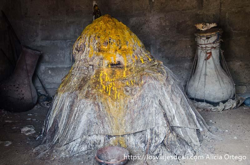 representación de dios lehva como un montón amorfo cubierto de telas y una sustancia amarilla derramada en la cabeza ceremonia vudú