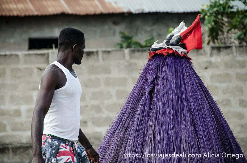 sacerdote con camiseta blanca frente a una máscara zambeto igual de alta que él hecha con fibras teñidas de morado ceremonia vudú