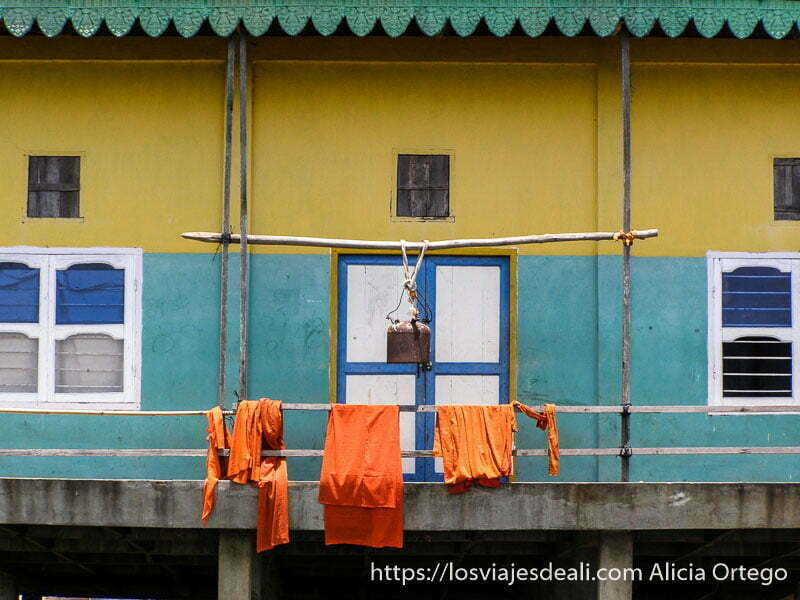 balcón y ventanas de templo budista con ropas naranjas de monjes secándose y una campana en camboya