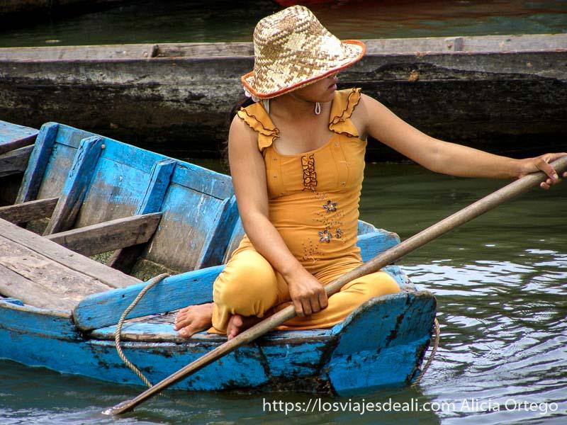 mujer con vestido amarillo y sombrero remando en una barca azul excursión cerca de los templos de angkor