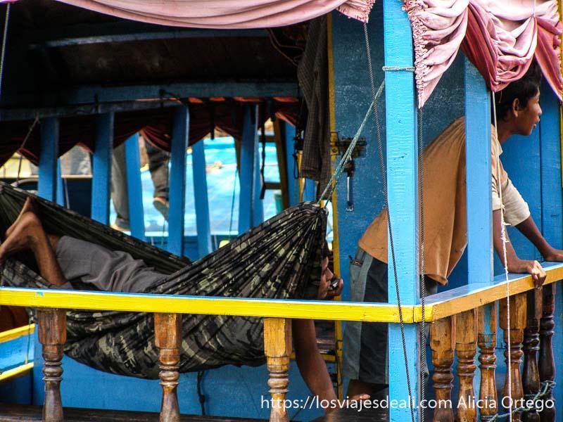 dos chicos en porche de su casa flotante pintada de azul uno de ellos en una hamaca camboya