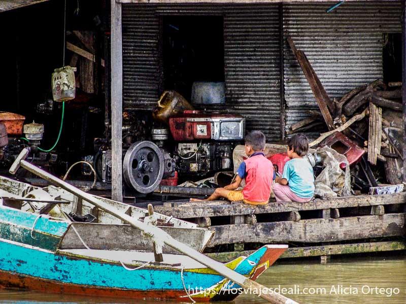 casa flotante con muchos cachivaches y una tele que están viendo dos niños pequeños de espaldas al río en camboya