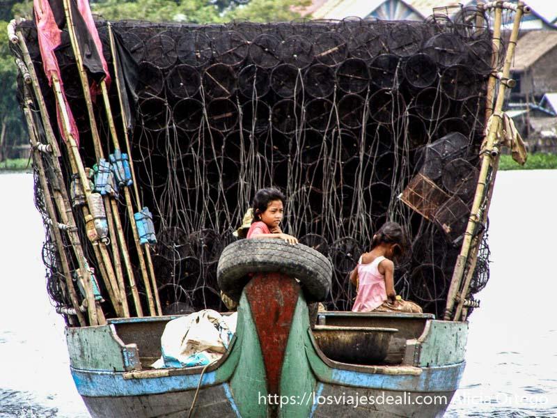 niñas en proa de una barca con montaña de redes de pesca y cartuchos de dinamita excursión cerca de los templos de angkor