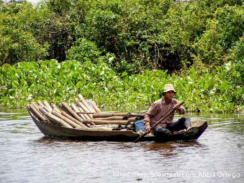 hombre llevando barca con maderas y detrás nenúfares excursión cerca de los templos de angkor