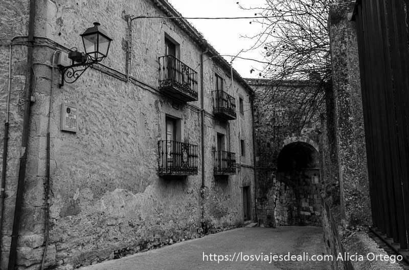 calle con caserón de piedra y al fondo un arco de muralla en sepúlveda