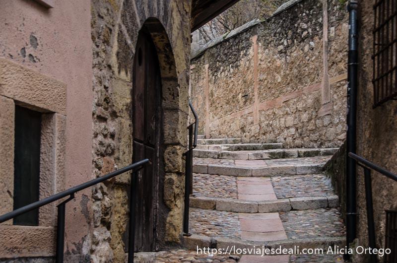 calle empedrada con escaleras y barandilla de hierro entre casas de piedra en sepúlveda