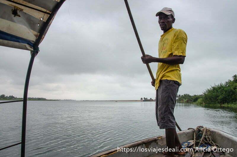 hombre conduciendo piragua con gran pértiga a modo de timón en río mono en benin