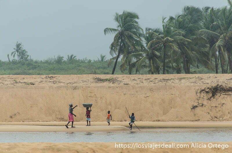 mujeres y niños junto a canal de agua y banco de arena con palmeras al fondo playas de benin