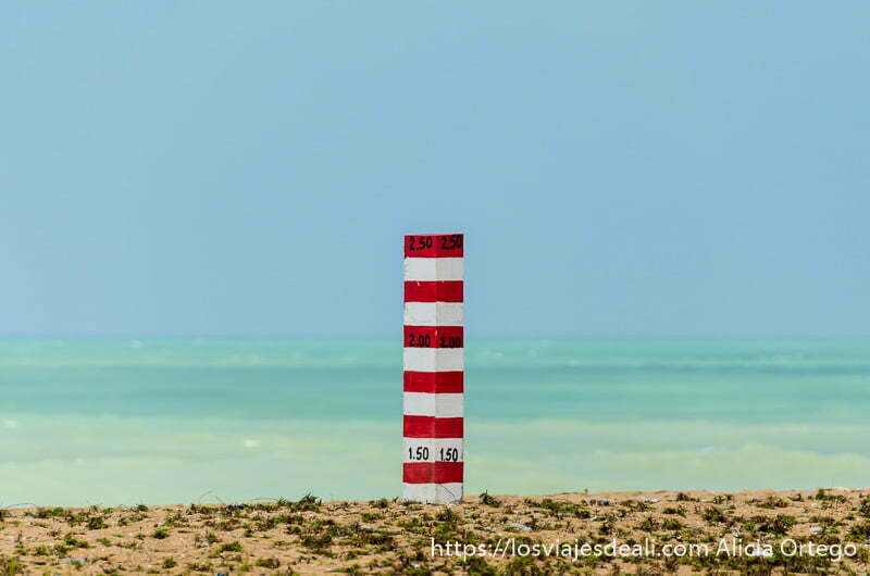 medidor de altura de  arena con rayas blancas y rojas y detrás el mar con colores verdes y turquesas intensos