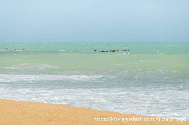 barcas en el mar de color verde y turquesa en playas de benin